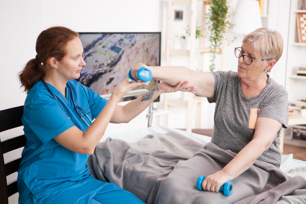 Caregiver helping using dumbbells for senior woman physiotherapy